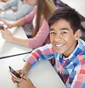 Middle school boy with cell phone in class