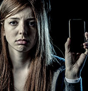 Girl holding phone cyber bullying