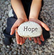 """Child holding """"hope"""" rock"""
