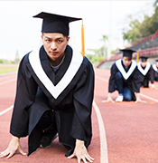 Graduates cap and gowns on race track